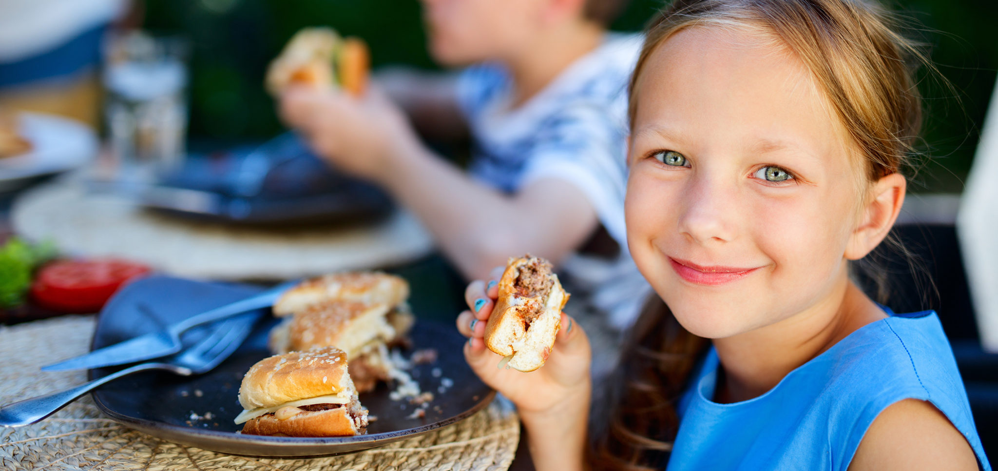 Little girl eating burger